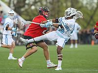 Baltimore, MD - April 28, 2018: Johns Hopkins Blue Jays Daniel Jones (23) gets hit by a Maryland Terrapins defender during game between John Hopkins and Maryland at  Homewood Field in Baltimore, MD.  (Photo by Elliott Brown/Media Images International)