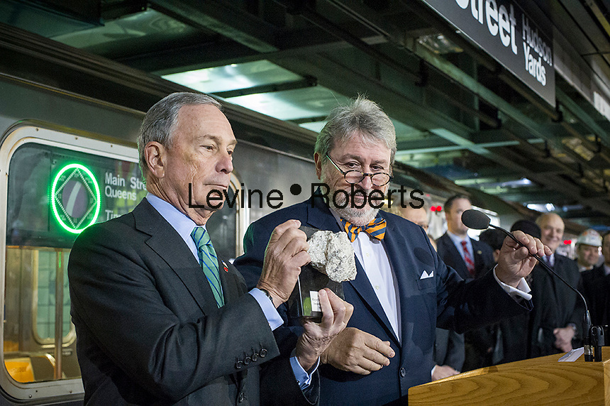 NYC Mayor Michael Bloomberg, left, receives a chunk of the tunnel from President of the MTA Capital Construction Corporation, Mike Horodniceanu, right, at the new 34th Street-Hudson Yards terminal station on the 7 Subway line extension in New York on Friday, December 20, 2013. The new tunnel from Times Square, which will open in the Fall of 2014,  terminates 108 feet below street level at West 34th Street and Eleventh Avenue rat the doorstep of the rezoned 45 block Hudson Yards development. (© Frances M. Roberts)