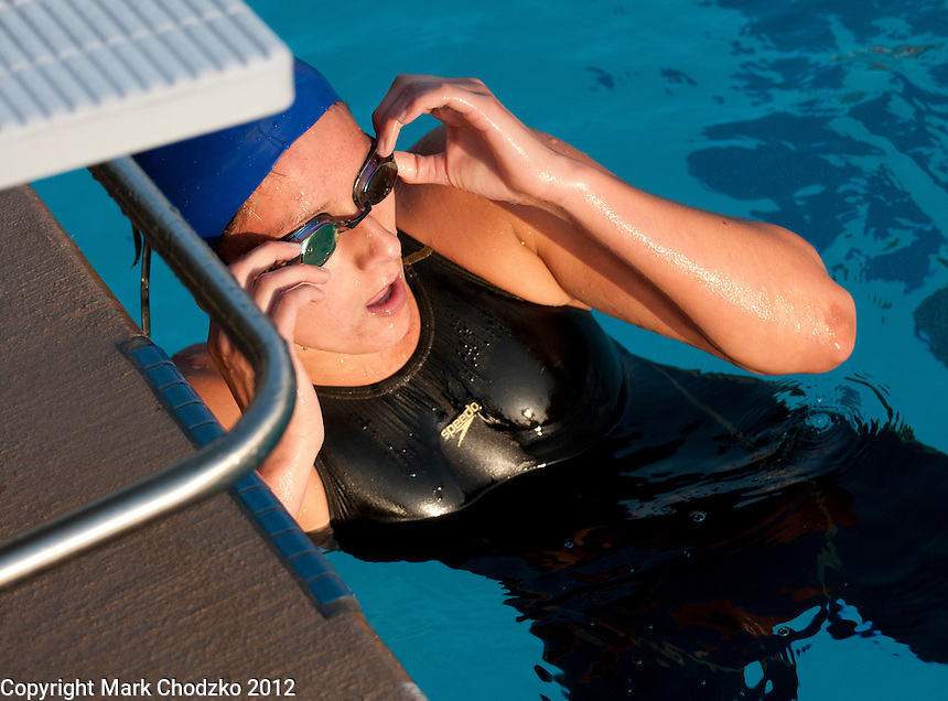 Swimmer looks anxiuosly at the board to check her time.