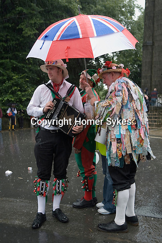 August summer rain. Musicians playing for a team of Morris men who are dancing during a rain storm. Uppermill Saddleworth Yorkshire UK 2012