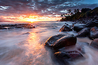 Colorful sunset reflecting off the water of a rocky shoreline at Waimea Bay, North Shore, Oahu