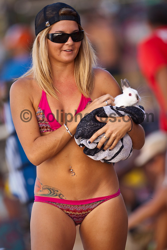HALEIWA, HI (Nov. 28, 2009) -- A girl with her pet rabbit at the WCT Gidget Pro at Sunset Beach was won today by Hawaiin surfer Carissa Moore (HAW). Runner up was Sally Fitzgibbons (AUS) with newly crown 2009 World Professional Surfing Champion Stephanie Gilmore (AUS) with Alana Blanchard (HAW) in fourth...Gilmore won the 2009 Title when Coco Ho (HAW) failed to advance from the semi finals. It is Gilmore's third straight world title win... The northern hemisphere winter months on the North Shore signal a concentration of surfing activity with some of the best surfers in the world taking advantage of swells originating in the stormy Northern Pacific. Notable North Shore spots include Waimea Bay, Off The Wall, Backdoor, Rocky Point, Log Cabins, Rockpiles and Sunset Beach... Ehukai Beach is more  commonly known as Pipeline and is the most notable surfing spot on the North Shore. It is considered a prime spot for competitions due to its close proximity to the beach, giving spectators, judges, and photographers a great view...The North Shore is considered to be one the surfing world's must see locations and every December hosts three competitions, which make up the Triple Crown of Surfing. The three men's competitions are the Reef Hawaiian Pro at Haleiwa, the O'Neill World Cup of Surfing at Sunset Beach, and the Billabong Pipeline Masters. The three women's competitions are the Reef Hawaiian Pro at Haleiwa, the Gidget Pro at Sunset Beach, and the Billabong Pro on the neighboring island of Maui...Photo: Joliphotos.com