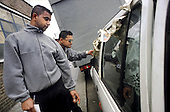 Neighbourhood Wardens employed by Tower Hamlets Council inspect a dumped car in Bethnal Green.
