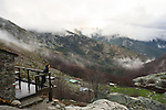 A woman enjoys the view from a mountain hut while hiking late in the year in Corsica.