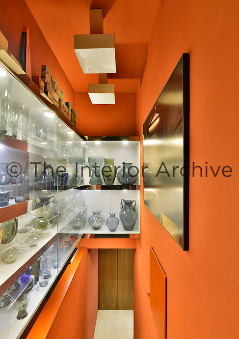 A collection of glassware is displayed on the shelves of a built-in glass cabinet, which is inside a small room painted a vibrant orange.