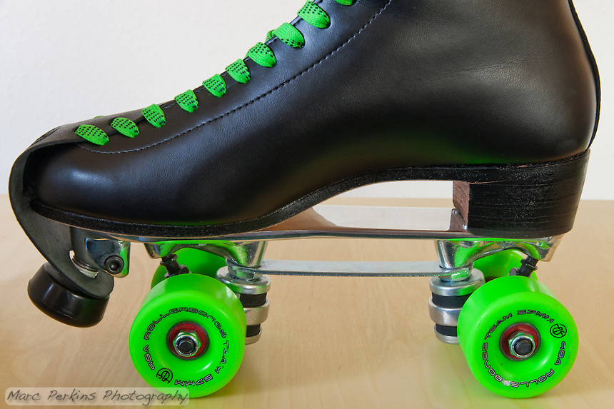 "Michelle's current pair of roller skates.  The boots are Riedell 220's in black, the plate is a Sure Grip Classic plate with toe stop and ""jump bar"", and the wheels are Rollerbones 98A 57mm in green.  The laces are green waxed hockey laces.   The wheels have Bones China Reds bearings, and there is a Riedell leather toe protector strap installed."