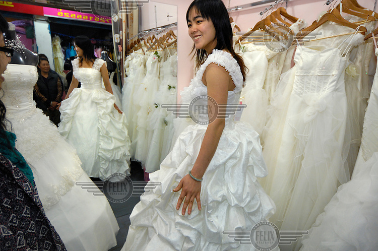 Bride-to-be trying on a wedding dress at a stall in a market devoted to selling wedding dresses, feeding a new trend of brides who are buying their dresses rather than hiring them.