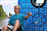 Jakub Bures am Steuer / Zwei junge Tschechen haben 6.000 Plastikflaschen gesammelt, um darauf ein Abenteuer zu erleben. Sie haben ein Boot gebaut und fahren damit die Elbe hinunter, bis nach Hamburg.