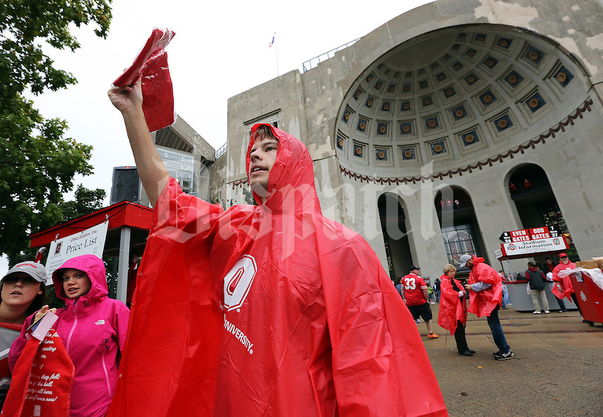 Ohio State senior Zach Eardley peddles scarlet ponchos for the student organization Ohio Staters Inc. outside Ohio Stadium prior to the NCAA football game against Florida A&M in Columbus on Sept. 21, 2013. (Adam Cairns / The Columbus Dispatch)