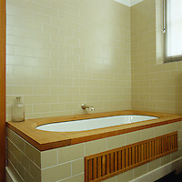 The bath is clad in tiles to match the walls and topped by a warm wooden surround