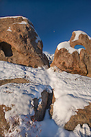 711700263 moonset at sunrise between snow covered granite boulders with the cloud-covered eastern sierras in the background seen from the alabama hills blm protected lands in kern county california