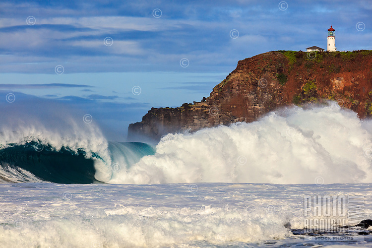 A wave explodes into white in front of the Kilauea Lighthouse and Kilauea Point at Secrets (or Secret, or Kauakea) Beach, Kaua'i.
