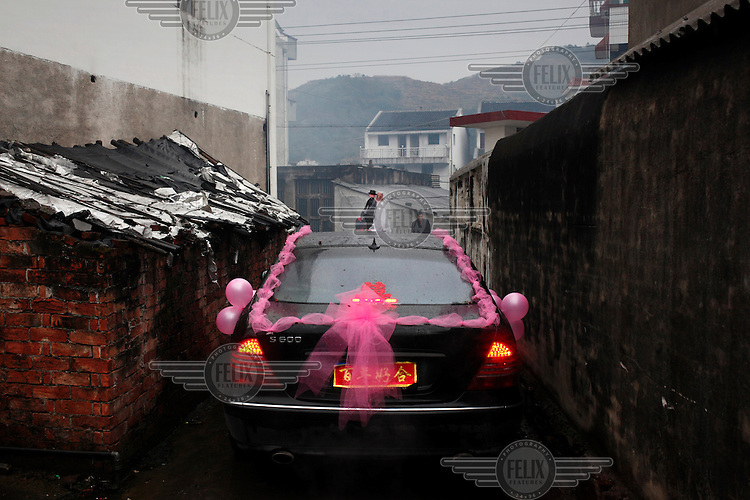 A large Mercedes car, decorated for a wedding, that can barely fit in the narrow lanes of the bride's village.