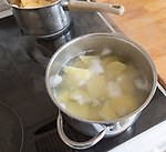 Looking down close up saucepan of potatoes boiling in water