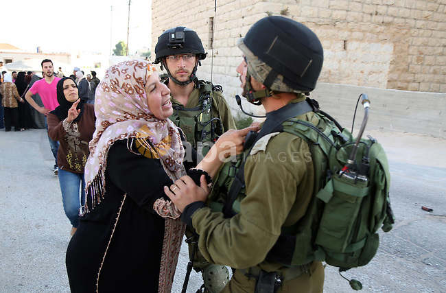 A Palestinian woman argues with Israeli soldiers in the village of Kafr Malik, northeast of Ramallah on June 14, 2015, after clashes that resulted in the death of 21-year-old Palestinian Abdallah Ghanayem. An army spokesman said that the Palestinian had died after he threw an incendiary device at a jeep and the vehicle overturned on him. Palestinian security sources said, Israeli soldiers killed Ghanayem by hitting him with their jeep during clashes near Ramallah in the occupied West Bank. Photo by Shadi Hatem