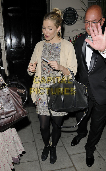 "SIENNA MILLER.Leaving after the evening performance of ""Flare Path"", Theatre Royal Haymarket, London, England, .31st May 2011..full length beige nude cardigan grey gray print dress black tights pen ankle boots bag hair up bun .CAP/CAN.©Can Nguyen/Capital Pictures."