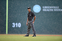 Umpire Harley Acosta watches as a sudden downpour begins in a game between the Greenville Drive and the Rome Braves on Friday, August 3, 2018, at Fluor Field at the West End in Greenville, South Carolina. There was a 90-minute rain delay. (Tom Priddy/Four Seam Images)