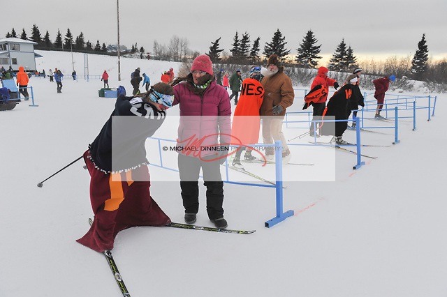 At left, Eagle River's Helen Wilson doubles up on her blanket wrap as she tries to keep warm prior to a sprint race during the Service Snowball races at Kincaid Park Saturday, Dec. 3, 2016.  Photo by Michael Dinneen for the Star.