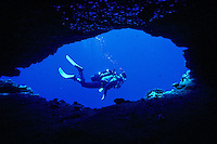 Scuba divers explore lava tubes and other unique geologic formations in Hawaii's underwater world.