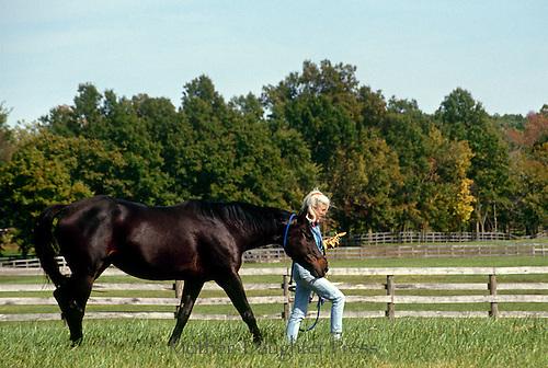 Mature woman leading horse through field