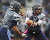 Plainview JFK quarterback No. 7 Kevin Pastier, right, hands off to running back No. 15 Nico Mueller during a Nassau County Conference I varsity football game against Port Washington at Plainview JFK High School on Saturday, October 3, 2015. Mueller rushed for four touchdowns in the first half to lead the Hawks to a 42-0 win.<br /> <br /> James Escher