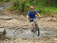 NWA Democrat-Gazette/ANDY SHUPE<br /> Kenneth Glenn of Culcord, Okla., rides across Lee Creek Saturday, Sept. 19, 2015, during the Northwest Arkansas Mountain Bike Championships at Devil's Den State park.