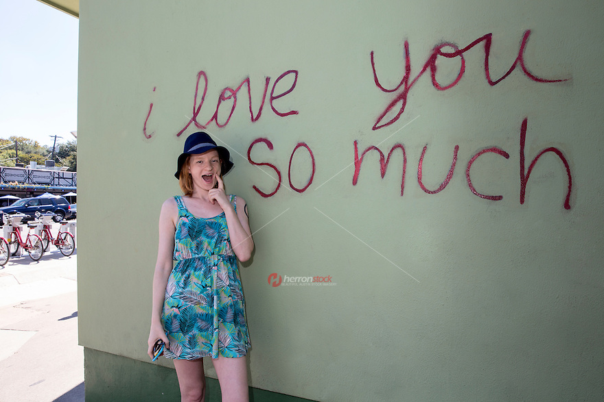 "An Austin local poses in front of the famous ""I love you so much"" mural in South Congress, Austin, Texas - Stock Image."