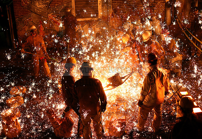 Sparks fly after molten iron was poured into a cast made from a tree stump. The University of Kentucky's art community, including students, alumni and instructors, made sculptures out of iron at UK's 19th annual Iron Pour.
