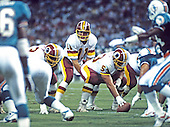 Washington Redskins quarterback Mark Rypien (11) calls signals as he prepares to take the snap from center Jeff Bostic (53) during a pre-season game against the Miami Dolphins at RFK Stadium in Washington, D.C. on August 25, 1989.  The Redskins won the game 35 - 21.<br /> Credit: Arnold Sachs / CNP