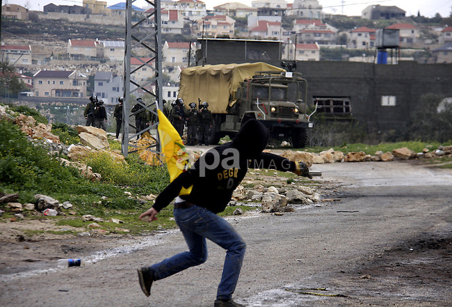 A Palestinian protester throws stones at Israeli soldiers during a demonstration against the expropriation of Palestinian land by Israel in the village of Kfar Qaddum, near the West Bank city of Nablus, on March 2, 2012.  Photo by Wagdi Eshtayah