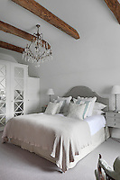 An antique crystal chandelier hangs from the beamed ceiling of a bedroom designed by Ham Interiors