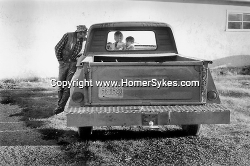 Butte Montana USA June 1971. Father leaning against family pick up truck talkin g to his children while waiting for his wife to arrive on the Greyhound bus.