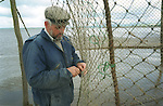 Walter Davidson, the last full-time salmon netter on the Solway in south-west Scotland, re-ties the pocket of the court of his stake net after checking for any caught fish, at Creetown, Dumfries and Galloway. Walter is a fourth generation salmon netter and lives in a bothy during the week during the salmon fishing season which lasts from May until September.