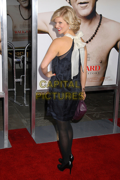 "ARDEN MYRIN.""Walk Hard: The Dewey Cox Story"" Los Angeles Premiere at Grauman's Chinese Theatre, Hollywood, California, USA..December 12th, 2007.full length black dress hand on hip purple bag purse looking over shoulder white sheer bow ribbon.CAP/ADM/BP.©Byron Purvis/AdMedia/Capital Pictures."