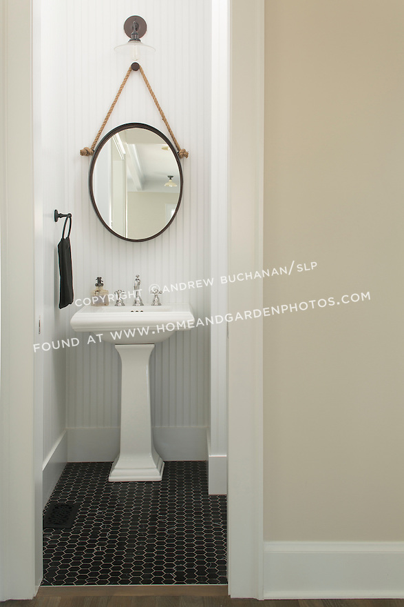 White beaded board walls and hexagonal black tile floor in a small powder room.  This image is available through an alternate architectural stock image agency, Collinstock located here: http://www.collinstock.com
