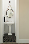 White beaded board walls and hexagonal black tile floor in a small powder room.