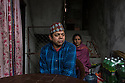 """Nepal - Kathmandu - Chom Prasad Panthi (left), 45-year-old, in his house in New Baneshwor, Kathmandu, where he owns a grocery shop along with his wife (right). Originally from the village of Arkhale-5 in the central district of Gulmi, two years ago Panthi went to Qatar to work as a driver in a private company. Instead, he was employed as a garbage collector, receiving 412 USD per month instead of the promised 631. After having worked for ten months for an average of 13 hours per day, Panthi walked out of his two-year-contract and returned to Nepal. """"I managed to repay my loan and cover my kids' tuition fees, nothing more than that"""", he says."""
