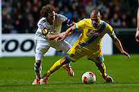 Swansea, UK. Thursday 20 February 2014<br /> Pictured: Gokhan Inler of Napoli is brought down bt Jose Canas of Swansea City <br /> Re: UEFA Europa League, Swansea City FC v SSC Napoli at the Liberty Stadium, south Wales, UK