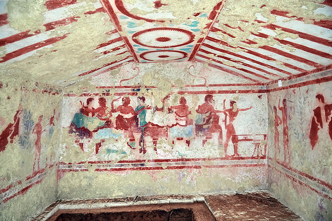 """Underground Etruscan tomb Known as """"Tomba Claudio Bettini no 5513"""" A single chamber with double sloping ceiling. In the tympanium on the back wall is a painted two lions, a two men lying on beds (Klinai) are  banquetting with two women bellow. On the dide walls are dancers and musicians. 5th century BC. Excavated 1967 , Etruscan Necropolis of Monterozzi, Monte del Calvario, Tarquinia, Italy. A UNESCO World Heritage Site."""