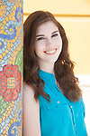 Portrait of a smiling teenage girl with dark brown hair next to a mosaic pole  in the East Village Arts District in Long Beach, CA, USA