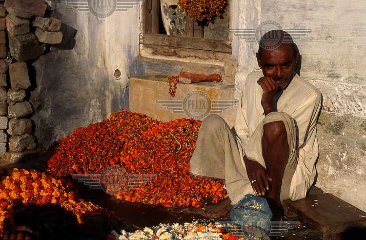 Man selling marigold flowers to be used as religious offerings.