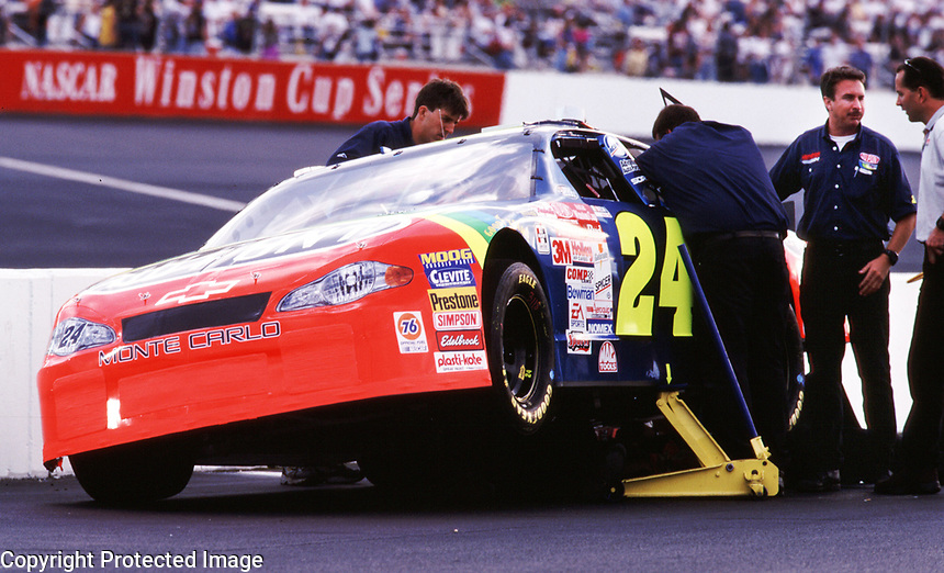 Robbie Loomis (second from right), crew chief for Jeff Gordon's Winston Cup team, oversees work on Gordon's car at Richmond International Raceway in Richmond, VA on Friday, 9/7/00.  Loomis was fined $25,000 by NASCAR when it was discovered that Gordon, who won the Richmond race, had used an illegal part on his race car.(Photo by Brian Cleary)