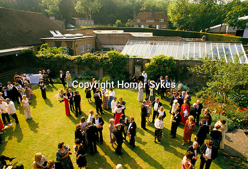 CROWDS AT GLYNDEBOURNE ENJOY THE EVENING SUNSHINE WHILE CHATTING & DRINKING ON THE LAWN,