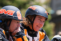 Close-up view of two female paddlers wearing helmets, watching the whitewater kayaking at Teva Mountain Games, Vail CO.