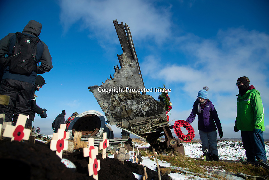 09/11/19<br /> <br /> Freya Kirkpatrick lays a wreath on the aircraft wreckage.<br /> <br /> Surrounded by fresh overnight snow, hikers gather, in one of the remotest areas of the Derbyshire Peak District, for a two minute silence and to lay wreaths and crosses on the wreckage of an American RB29 bomber, known  as 'Over-Exposed' which crashed on Bleaklow Moor near Higher Shelf Stones, killing all thirteen crew in November 1948. Piles of twisted metal have been piled up to form a makeshift memorial that lies next to whole engines, pieces of fuselage, wings, wheels and other twisted parts of aluminium that have lain on the moors for  71 years.<br /> <br /> Today prayers were said, a harmonica player performed the Last Post and Taps (the US equivalent) and members of the Woodhead Mountain Rescue teams remembered their forbears who were first to arrive at the crash scene after the bomber descended in low cloud hitting the high peak.<br /> <br /> All Rights Reserved: F Stop Press Ltd.  <br /> +44 (0)7765 242650 www.fstoppress.com