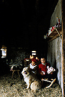 Two little girls and their dog Gigi at the entrance to the stone barn with the festively decorated table beyond
