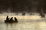 Opening day of fishing on Martha Lake at sunrise in fog with silhouetted fishermen in small boats fishing, Snohomish County Washington State USA