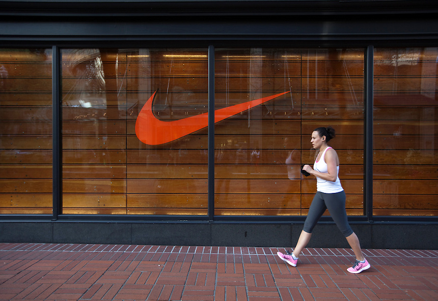 A pedestrian passes Nike's flagship store in downtown Portland, Oregon on Wednesday,  April 24, 2013. Confidence among consumers fell in April to a nine-month low as Americans grew more pessimistic about the outlook for the economy.  Photographer: Natalie Behring/Bloomberg News