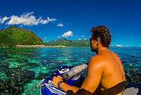 Looking to overwater bungalows in the lagoon (inside the reef) from aboard a jetski, Hilton Moorea Lagoon Resort, island of Moorea, French Polynesia.