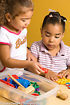 Preschool 3-4 year olds girl offering another girl a play dough cutter